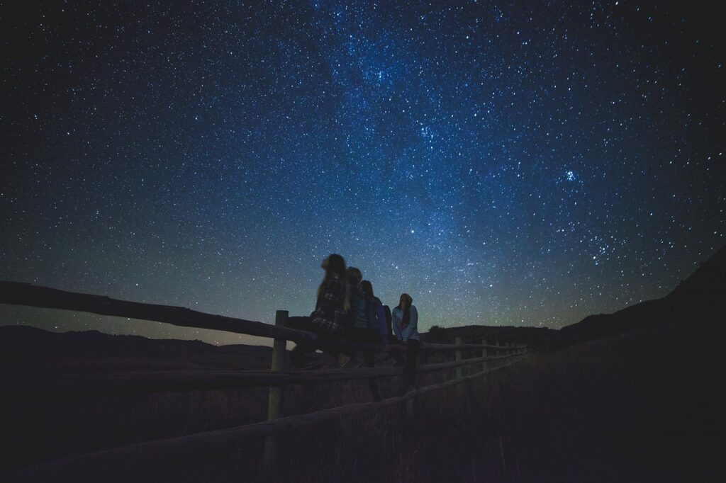 Alcune ragazze sono sedute insieme ed osservano le stelle